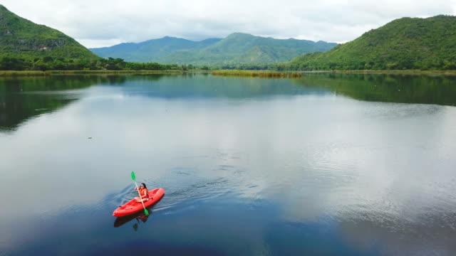 vídeos y material grabado en eventos de stock de mujer de kayak en el lago y la montaña en tailandia - kayak barco de remos