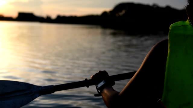 Kvinna som paddling på sjön i twilight