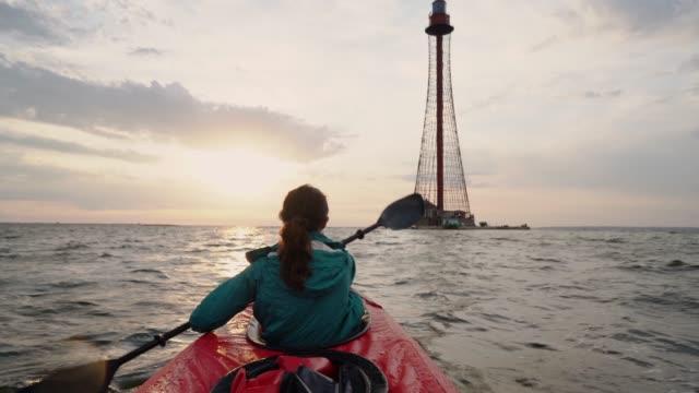vídeos y material grabado en eventos de stock de mujer kayak a faro al atardecer - kayak piragüismo y canotaje