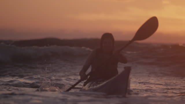 Woman kayaks through ocean waves at sunset, slow motion