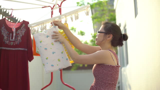 woman keep the clothes dry on a clothesline - prevenzione delle malattie video stock e b–roll