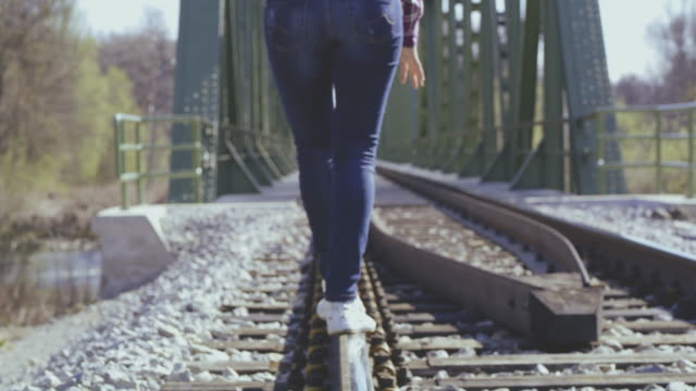 ws woman keeping the balance while walking on the railroad tracks - stability stock videos & royalty-free footage