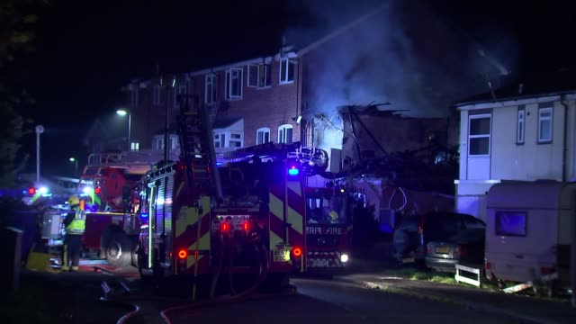 woman killed in suspected gas explosion in harrow; england: london: harrow: ext / night fire engine with flashing lights and firefighters at scene of... - harrow stock videos & royalty-free footage