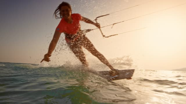 slo mo woman kiteboarding at sunset and waving into the camera - kiteboarding stock videos & royalty-free footage