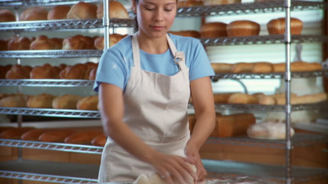 TU Woman kneading dough in bakery looks up and smiles at camera / racks of bread in background