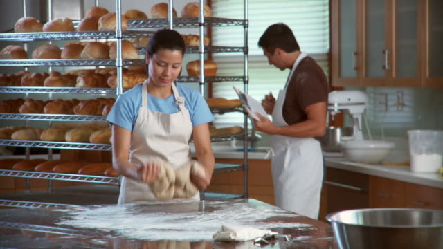 ms woman kneading dough while man holding clipboard pushes rack of bread in background - apron stock videos & royalty-free footage