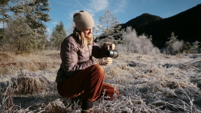 woman kneeing drinking a hot tea in the mountains - mitten stock videos and b-roll footage