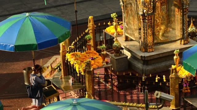 a woman kneel to pray at erawan shrine in the morning - エラワン聖堂点の映像素材/bロール