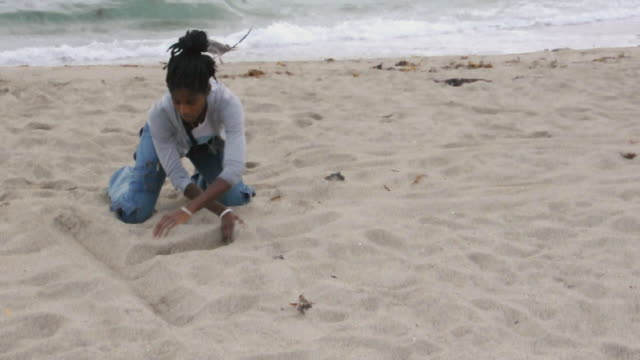 MS Woman kneeling and writing in sand on beach, Los Angeles, California, USA