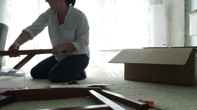pan woman kneeling on floor assembling a chair from flat pack. - instruction manual stock videos and b-roll footage
