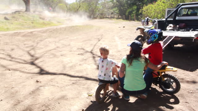 vídeos y material grabado en eventos de stock de a woman kneeling on the ground talking with a young boy on a dirt bike and another young boy on a wooden bike watching people ride around a dirt bike track - kelly mason videos