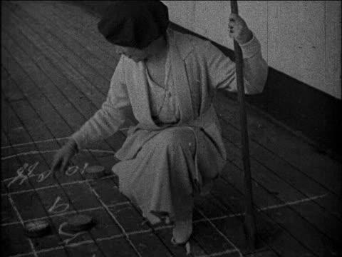 vídeos de stock e filmes b-roll de b/w 1930 woman kneeling + playing shuffleboard on deck of ocean liner / educational - ajoelhar
