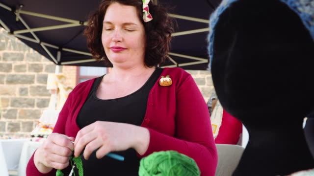 A woman knitting in a street market