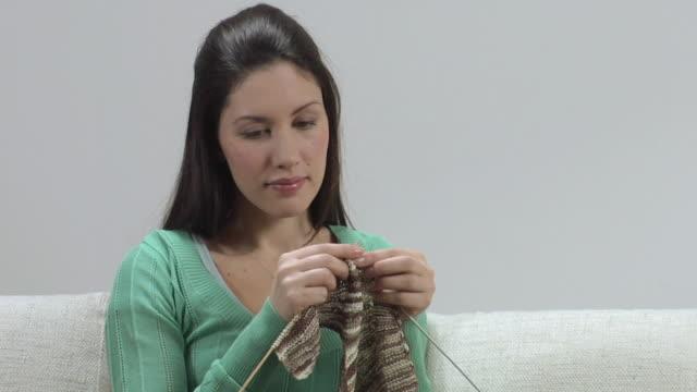 CU SLO MO Woman knitting on sofa / London, UK