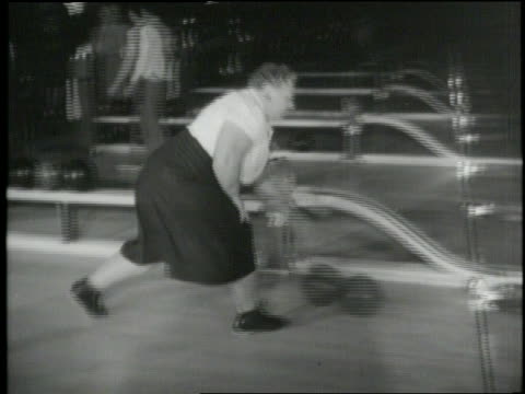 a woman knocks down bowling pins in the 1940s - ボーリング場点の映像素材/bロール