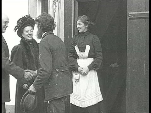 woman knocks on door and is greeted, they shake hands, man with beard invites them in, woman shakes hand out of window, young men come through door... - 1910 stock-videos und b-roll-filmmaterial
