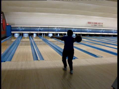 vídeos de stock, filmes e b-roll de woman knocks over remaining pins in bowling alley dallas - cancha de jogo de boliche