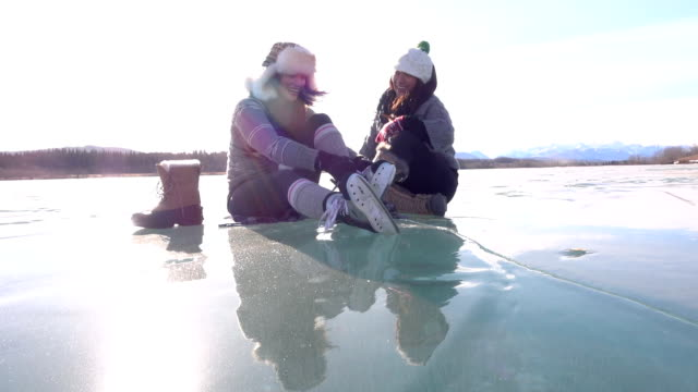 woman laces skates on frozen pond, with friend - mitten stock videos & royalty-free footage