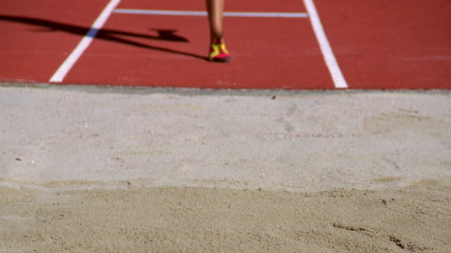 a woman lands in a sand pit after her attempt at the long jump. - salto in lungo video stock e b–roll