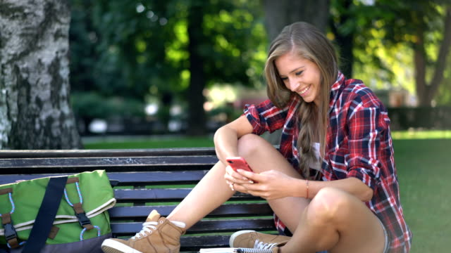Woman laughing and chatting online on her phone in the park.