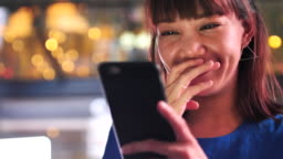 Woman laughing and Looking on mobile at night