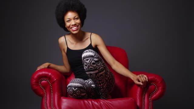 vídeos y material grabado en eventos de stock de woman laughing and moving around in red leather armchair - camisola