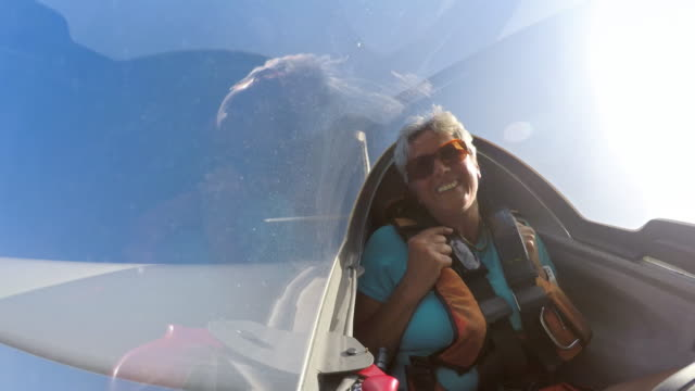 ld woman laughing in the back of the glider as it loops high in the sky - glider stock videos & royalty-free footage