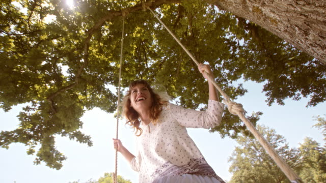 SLO MO PAN vrouw lachen op een schommel