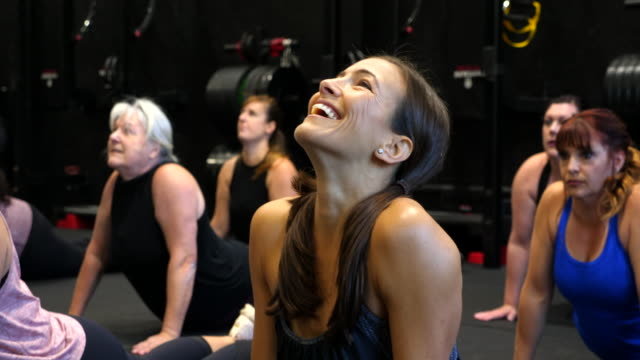 vidéos et rushes de ms woman laughing while stretching during fitness class in gym - performance athlétique