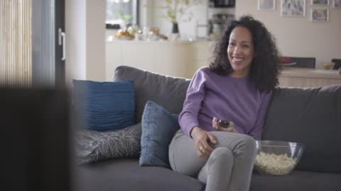 vídeos de stock, filmes e b-roll de mulher rindo enquanto assistindo tv no sofá - assistir tv