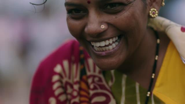 CU SLO MO. Woman laughs and smiles at camera.
