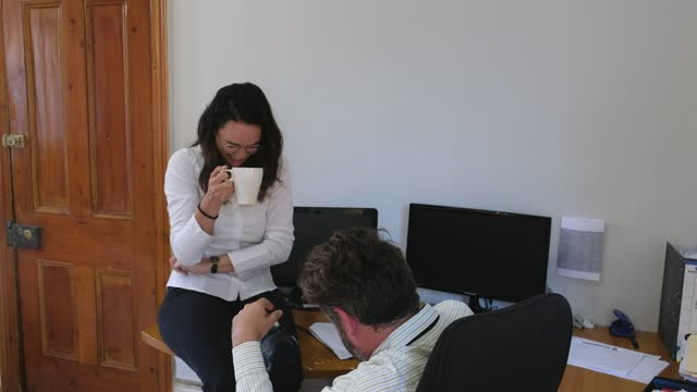 woman laughs and spills coffee all over herself and her colleague - blooper film clip stock videos & royalty-free footage
