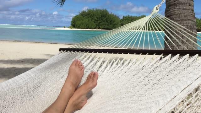 woman lay on a hammock relaxing in muri lagoon in rarotonga, cook islands - hammock stock videos & royalty-free footage