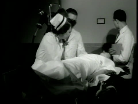 woman laying down on examining table doctors nurse ms doctors moving xray machine into position ms doctors looking at clipboard boston - examination gown stock videos and b-roll footage