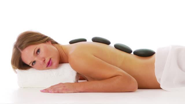 vídeos de stock e filmes b-roll de woman laying facedown at spa with hot rocks on back - cara para baixo