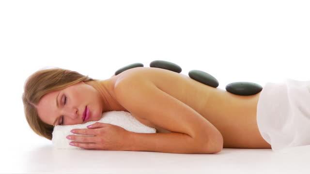 vídeos y material grabado en eventos de stock de woman laying facedown at spa with hot rocks on back - de cara al suelo