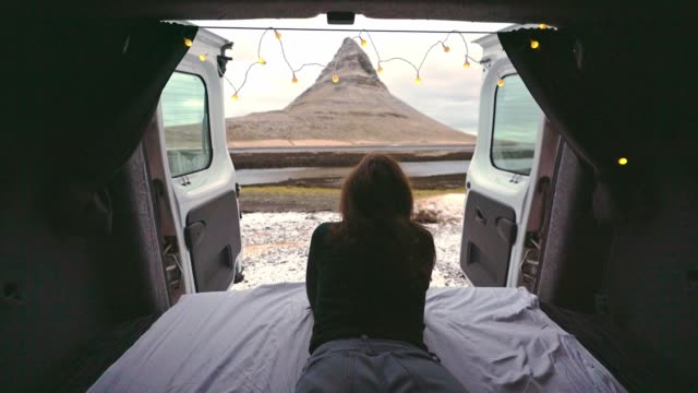 Woman laying in camper van and looking at Kirkjufell mountain in Iceland in winter