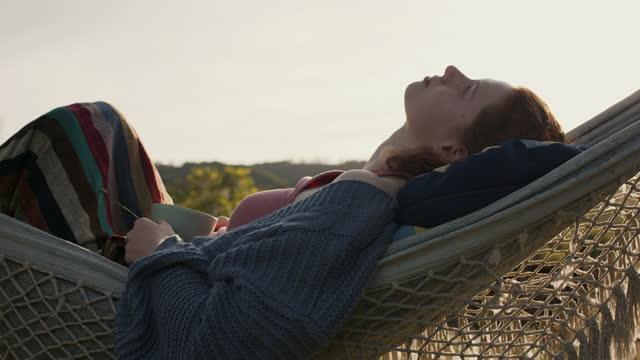 vídeos de stock e filmes b-roll de woman laying in hammock with tea cup - cabelo natural