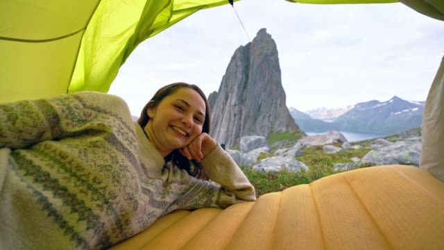 woman laying in tent with view of mountain on senja island - decor stock videos & royalty-free footage