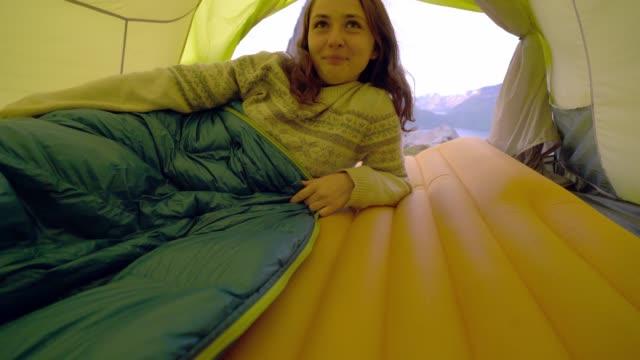 千蛇島の山の景色を望むテントに横たわっている女性 - 寝袋点の映像素材/bロール