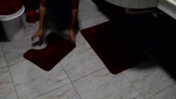 Woman laying mats on bathroom floor