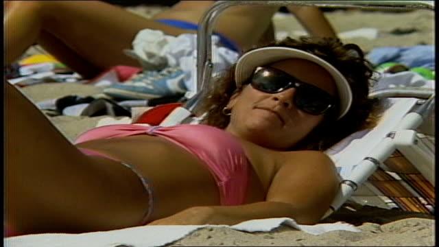 Woman Laying on Beach in Pink Bikini Sunglasses and Visor Smiling at Camera