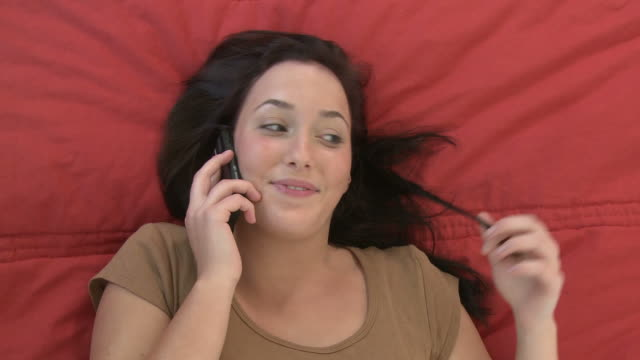 OH CU Woman laying on bed and twisting her hair as she talks on cell phone/ Berlin, Germany