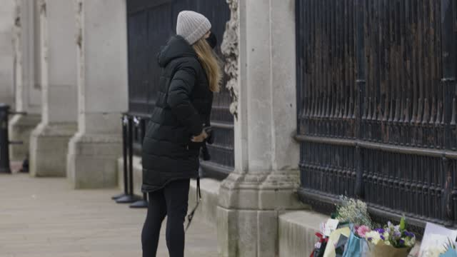 woman lays flowers at buckingham palace as tribute to prince philip, duke of edinburgh who died at age 99 on april 10, 2021 in unspecified, united... - monument stock videos & royalty-free footage
