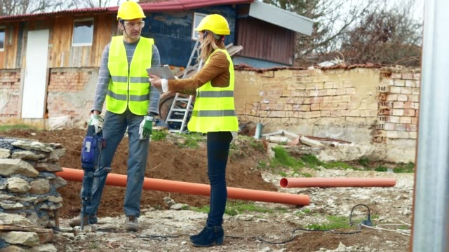 woman leader. a woman engineer giving orders to a construction worker using jackhammer. working on a construction site. drilling, construction site, construction industry, braking up a rock, - roadworks stock videos & royalty-free footage
