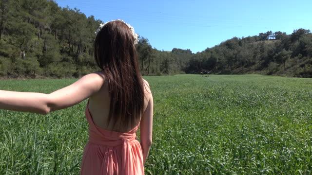 Frau, die ihren Freund durch Weizenfeld führt