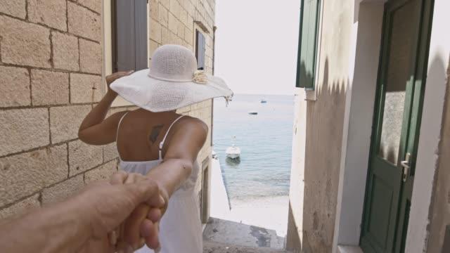 vídeos de stock e filmes b-roll de slo mo mulher liderando seu namorado para a praia - cidade pequena