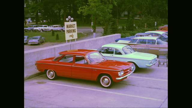 MS Woman leading young man to her car, man loading bag of groceries under hood in front of 1960 Chevrolet Corvair at supermarket parking lot / United States