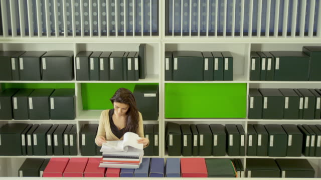 ha ws woman leafing through documents in office library - repetition stock videos and b-roll footage