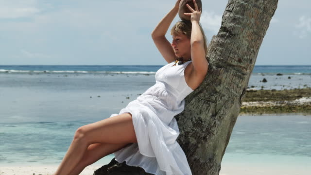 woman leaning against a palm tree in a white dress - isola di tahaa video stock e b–roll